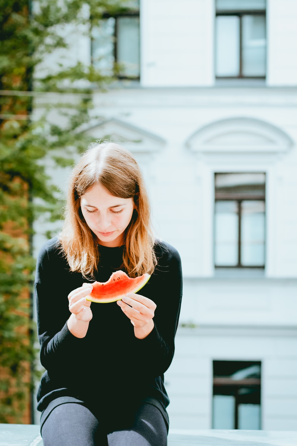 woman holding slice of watermelon while sitting on concrete bench outdoor