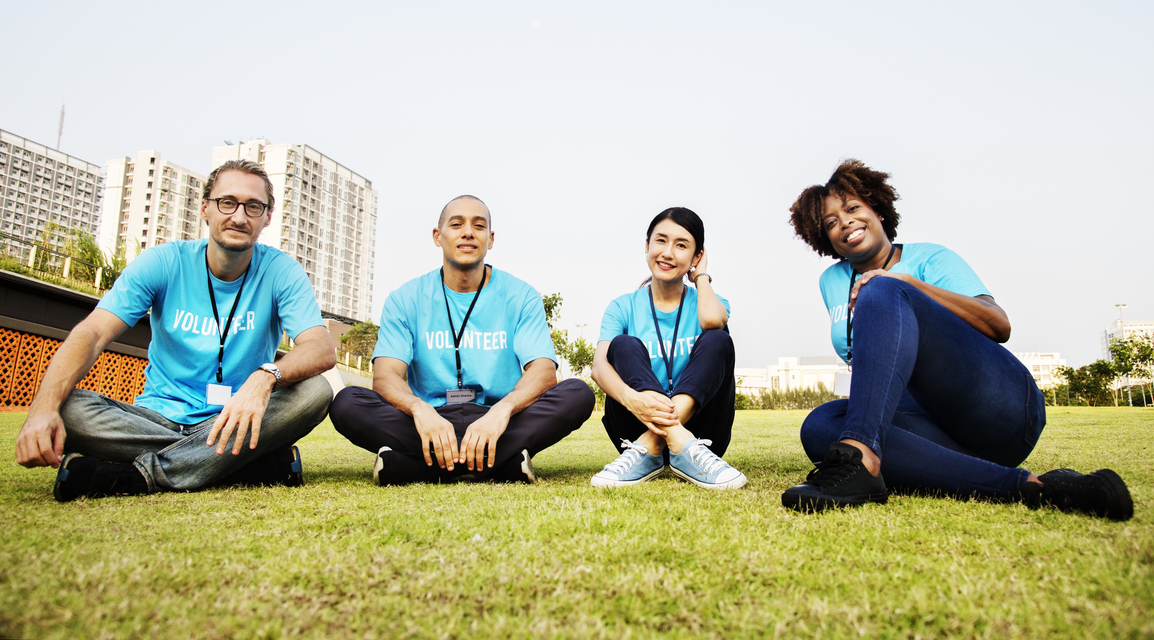 two men and two women sitting on green grass field during daytime