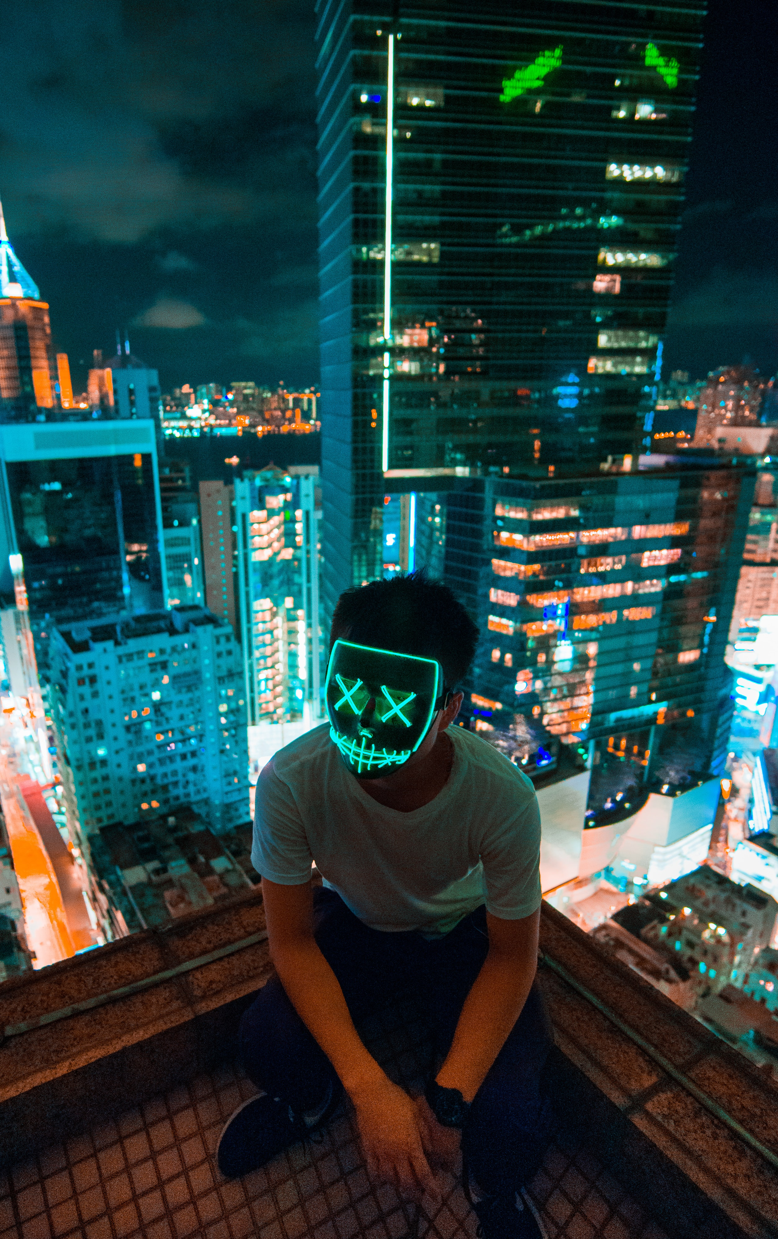 man wearing mask sitting on top of building