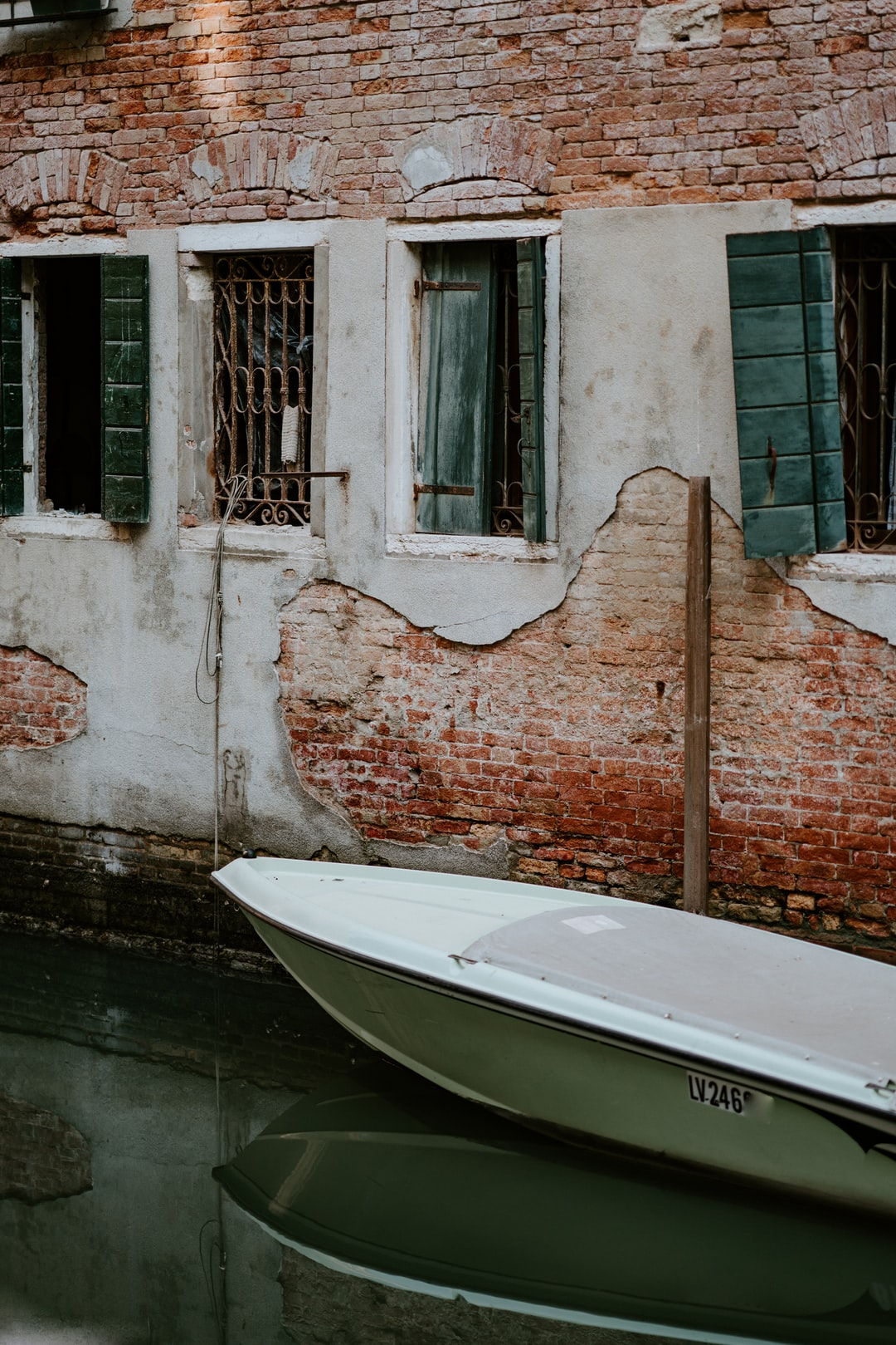 Boat moored by a worn brick wall in Venice