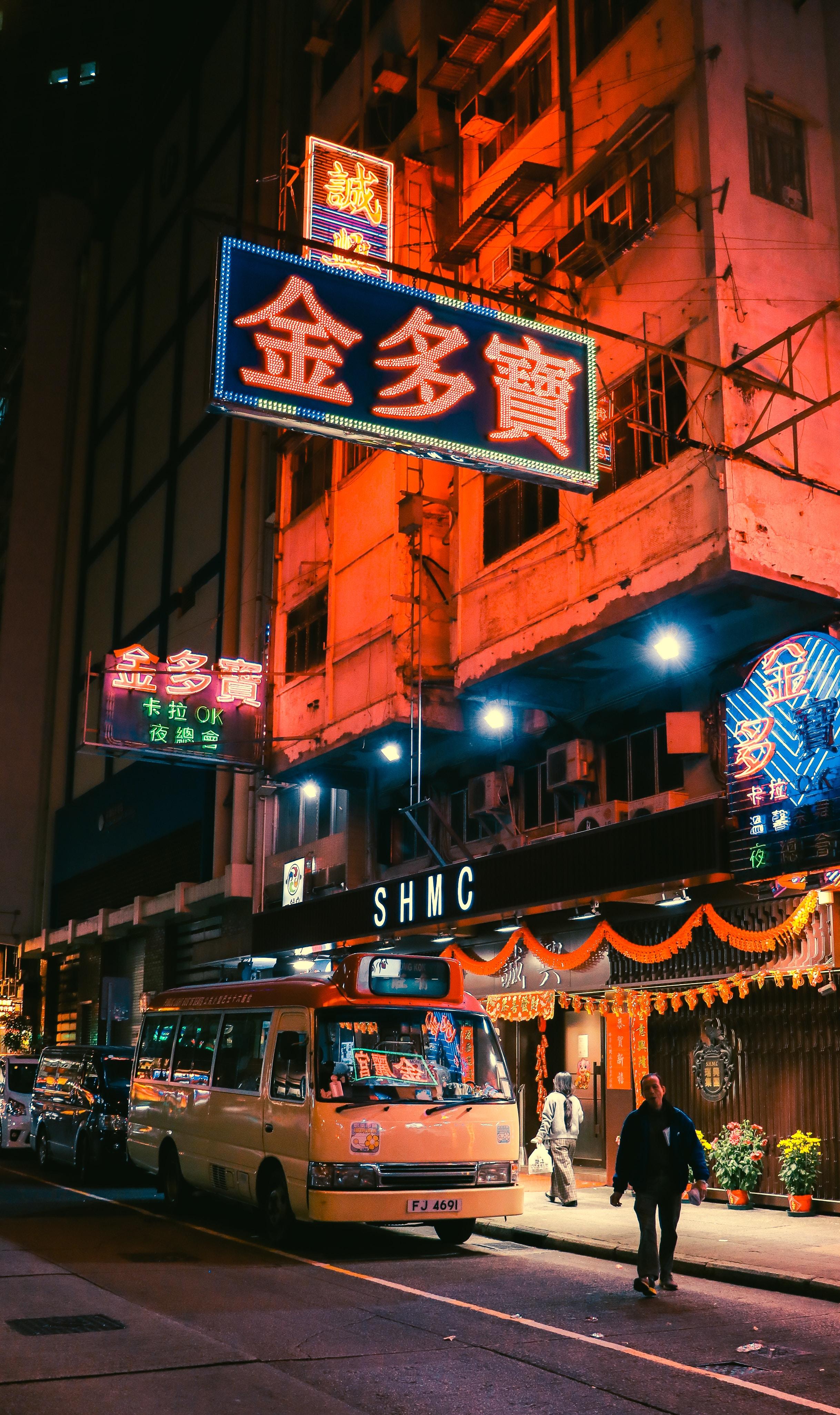 people walking on street near building during nighttime