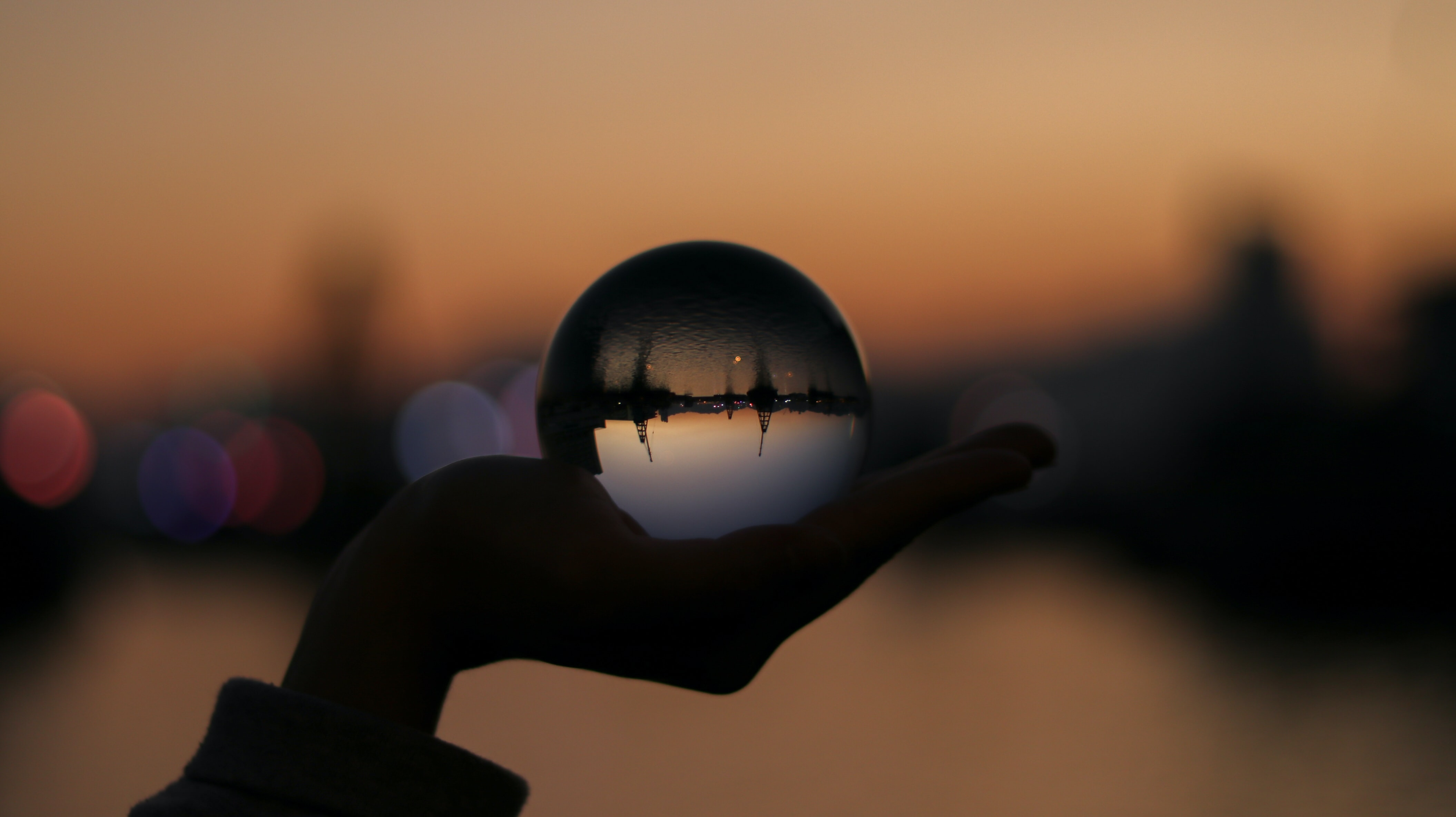person holding glass ball in selective focus photography