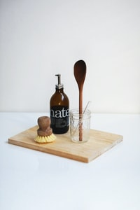 brown glass bottle beside clear glass jar on chopping board