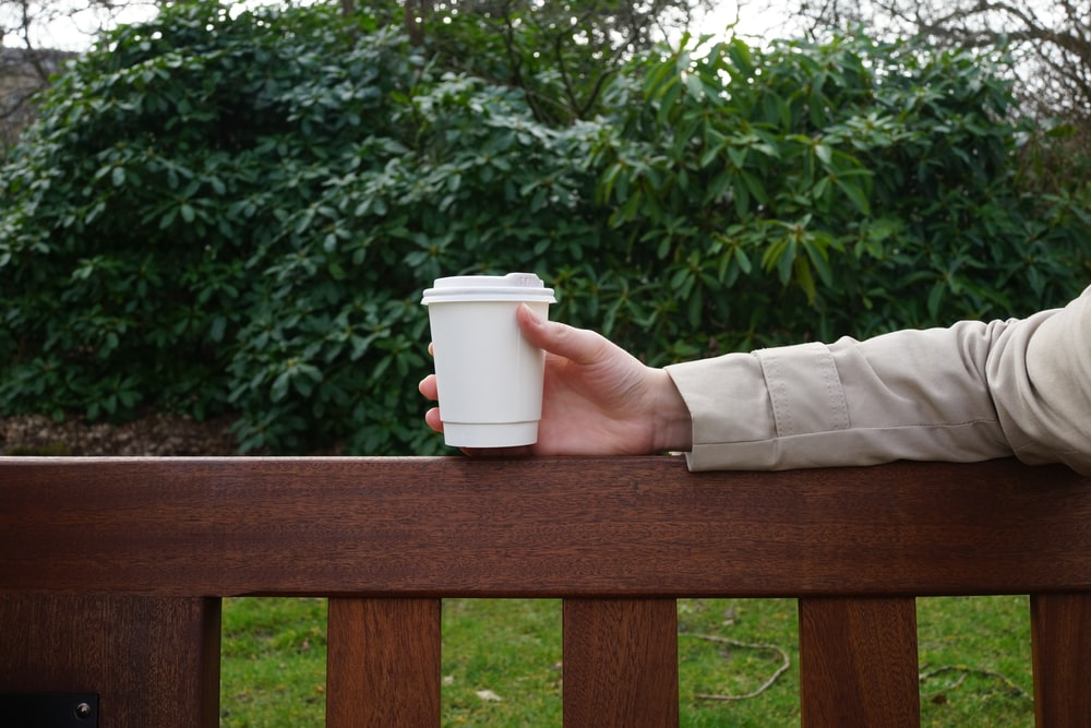 person holding white disposable cup on brown wooden railing