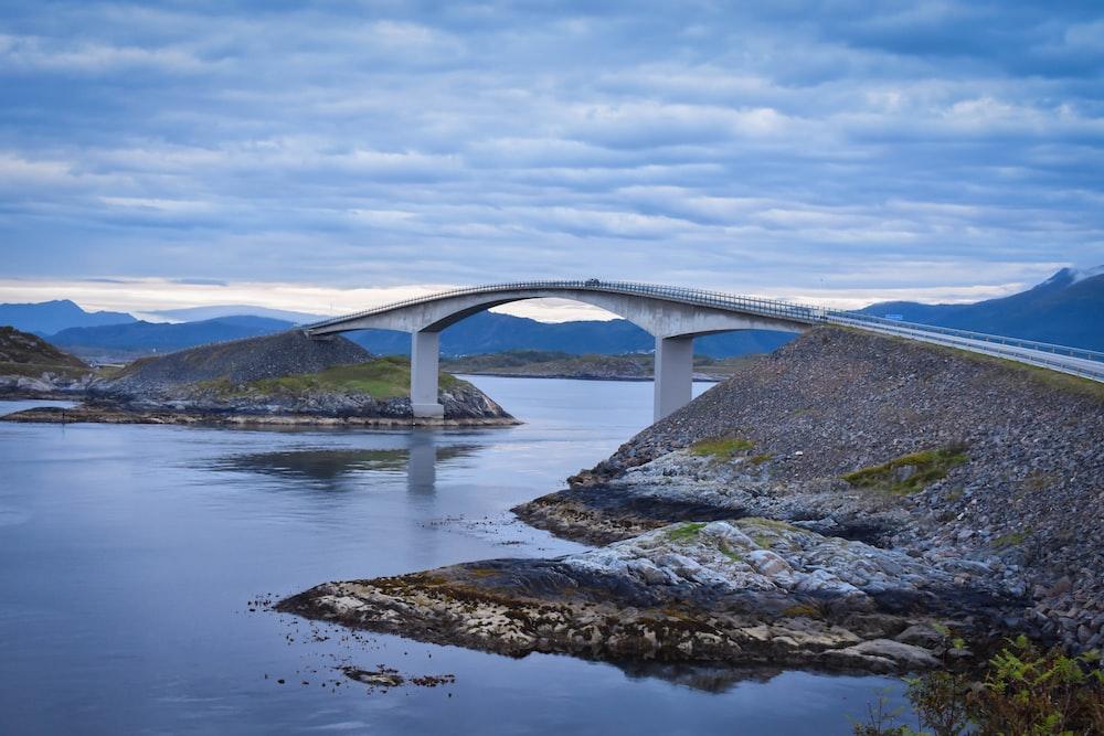 white concrete bridge under white and blue sky at daytime