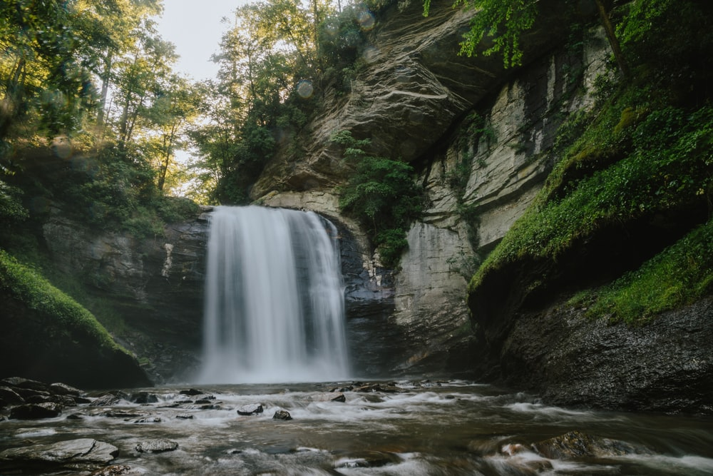 flowing waterfall with rocks and moss on side during daytime