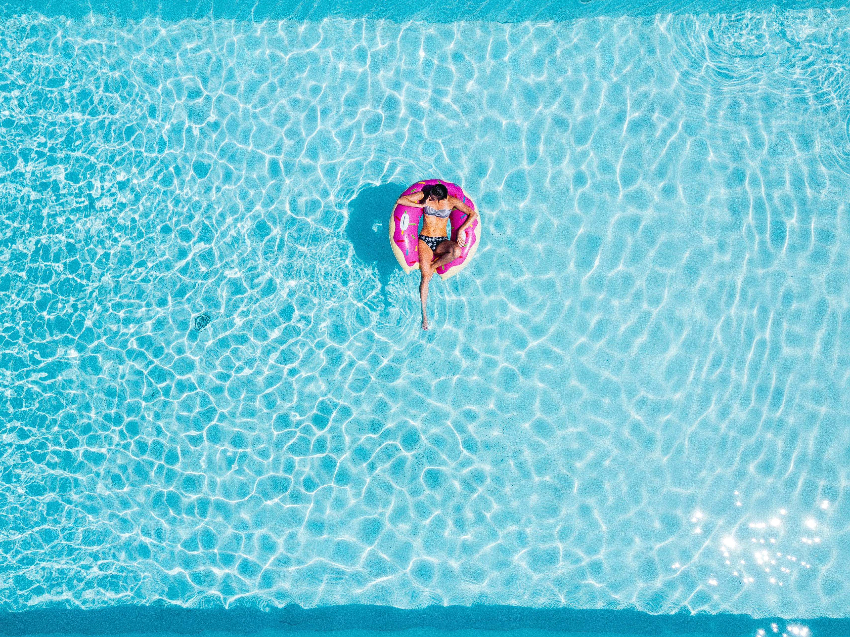 aerial photography of woman on pink swimming floats