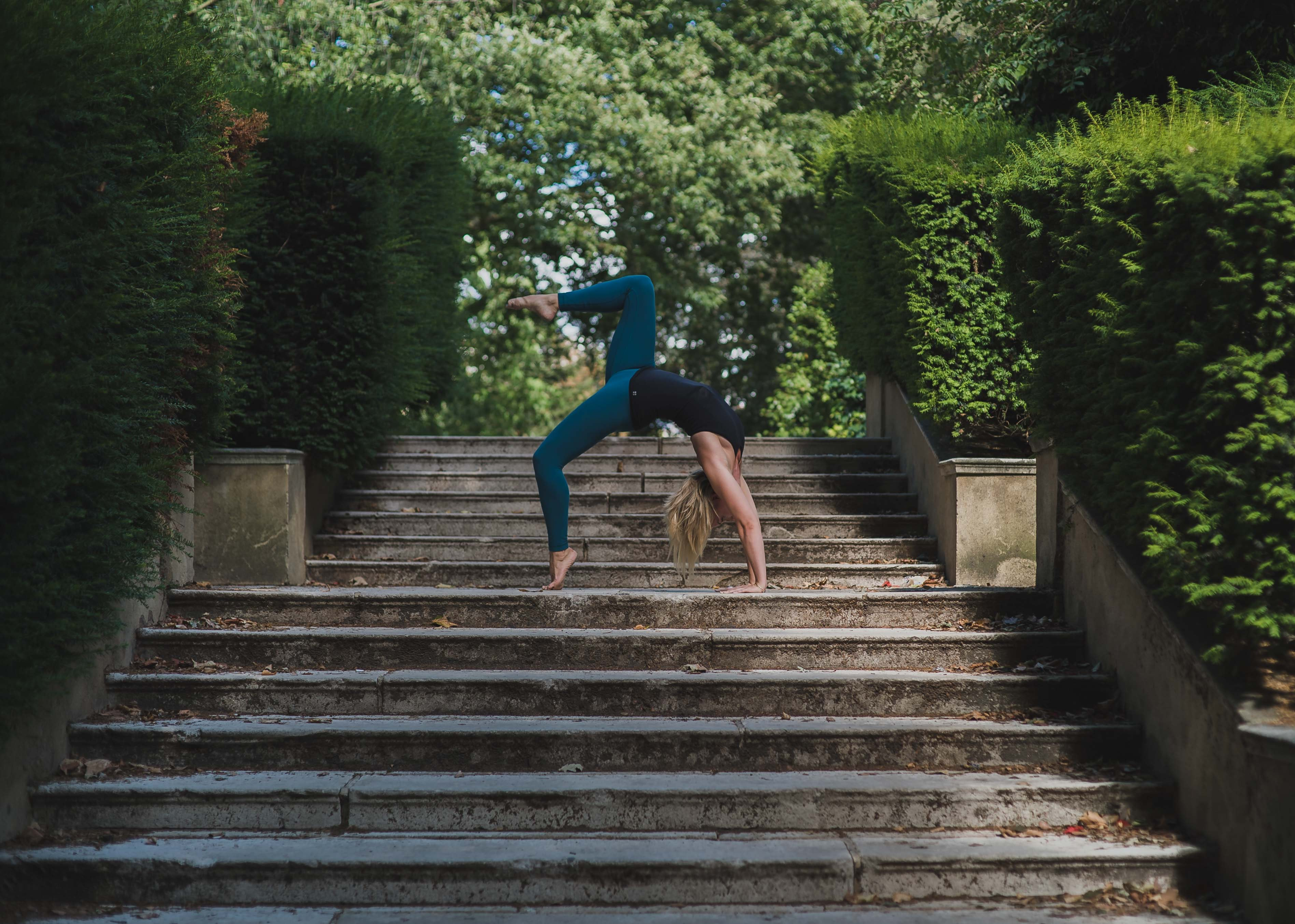 woman bending on gray concrete stair during daytime