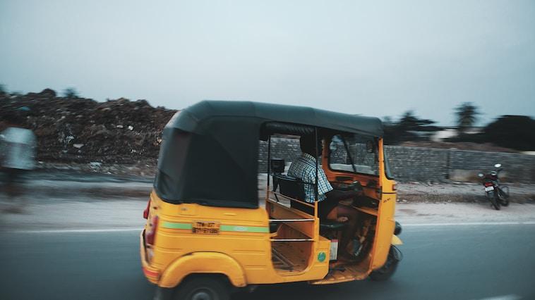 Autos Into Ambulances man riding auto rickshaw travelling on road
