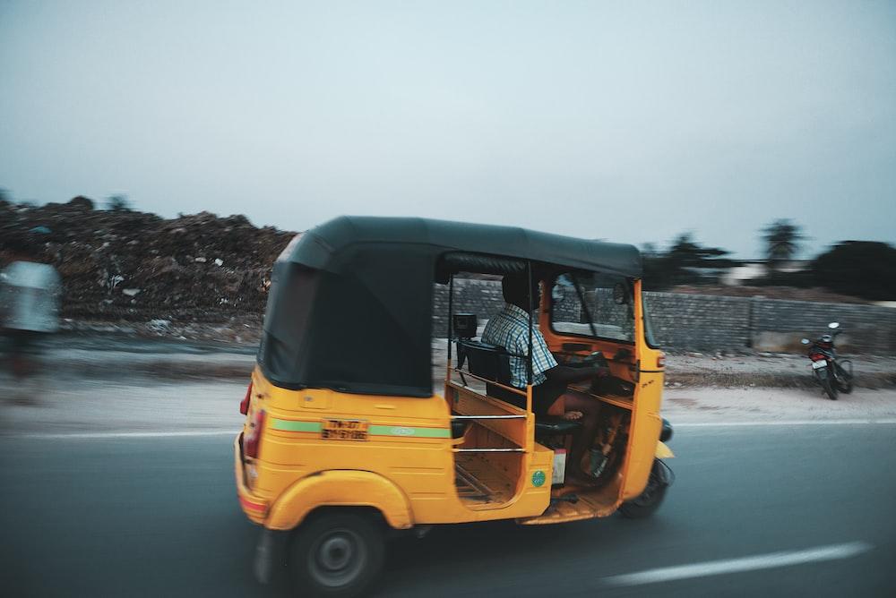 man riding auto rickshaw travelling on road