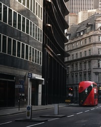 red bus in front of black painted building