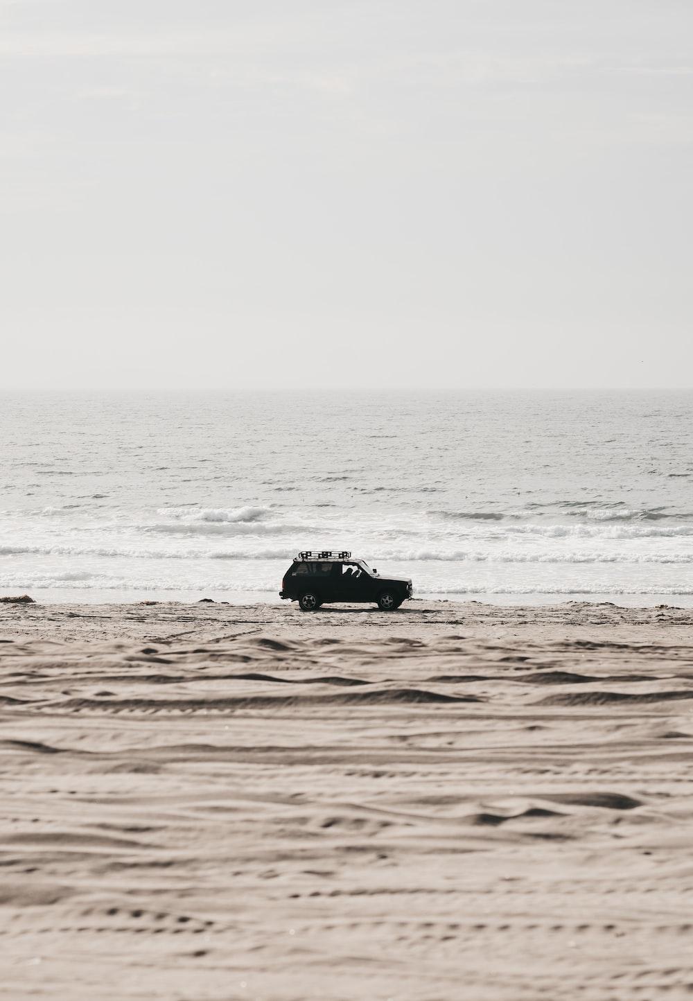 black SUV parked near seashore