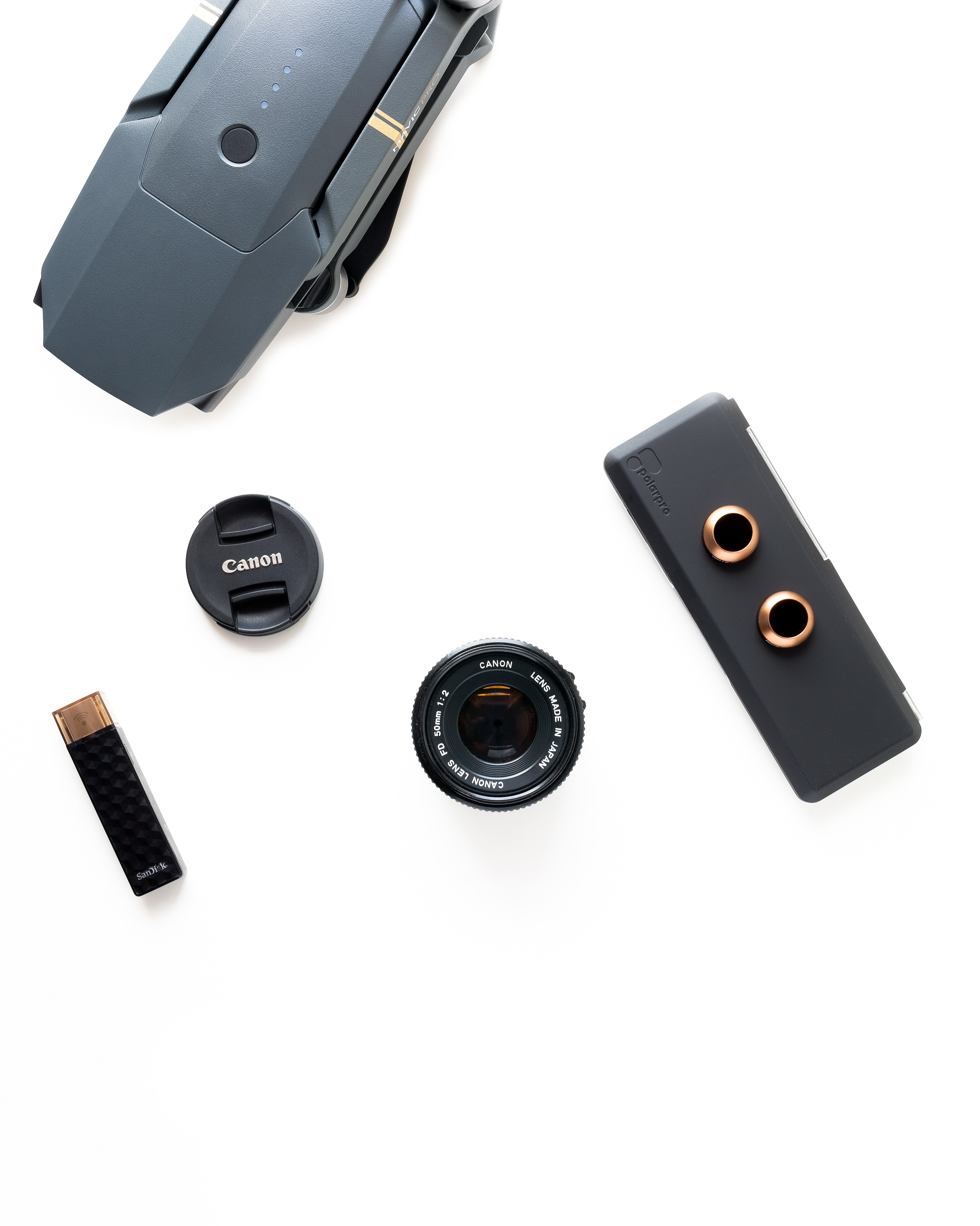 black Canon zoom lens on white surface near gray quadcopter drone