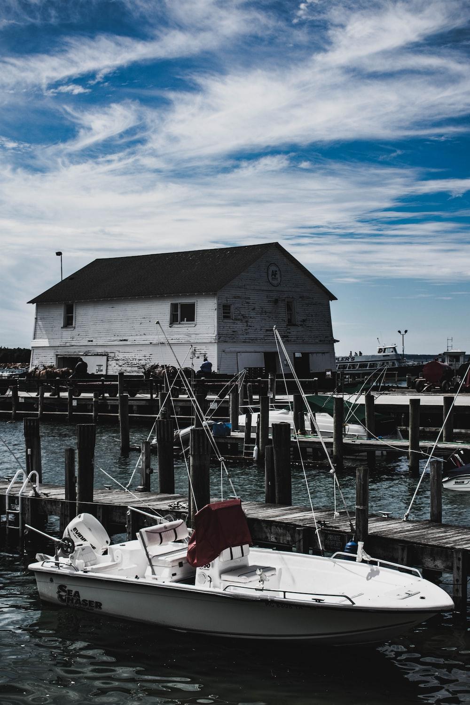 white powerboat near dock during daytime