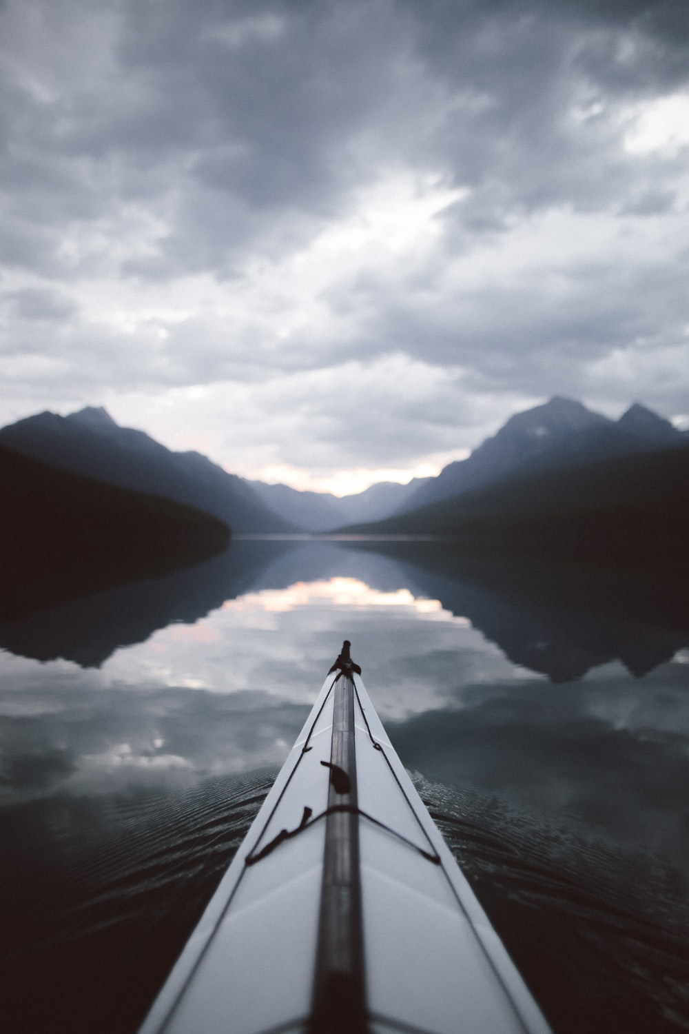 grayscale photo of body of water and mountains