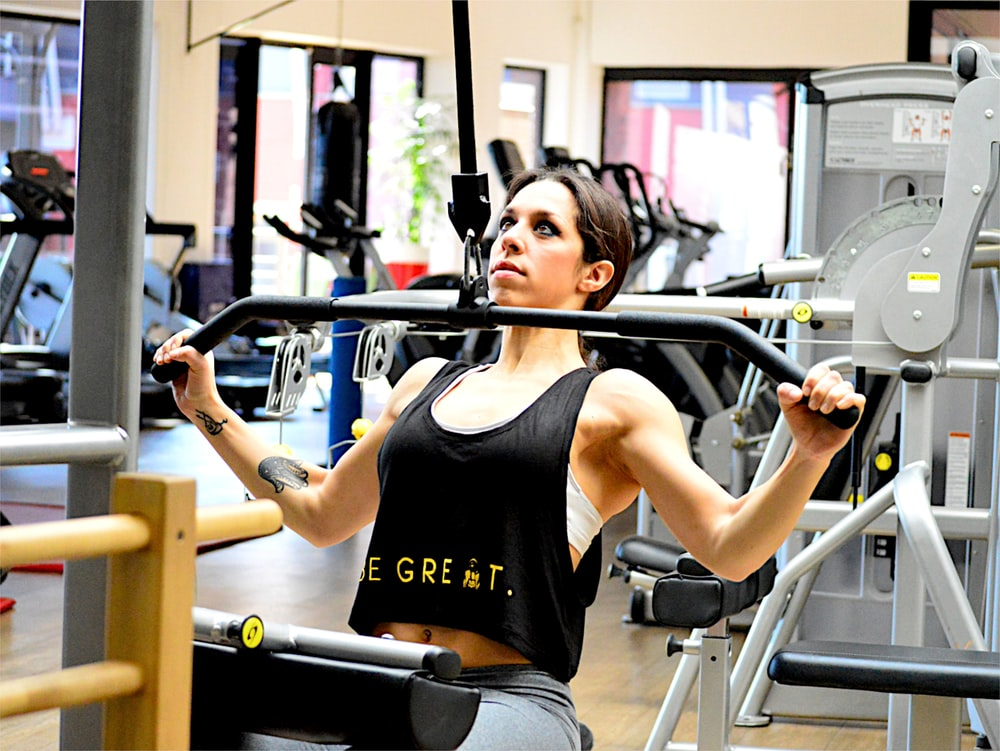 woman exercising using lateral pull down machine at daytime