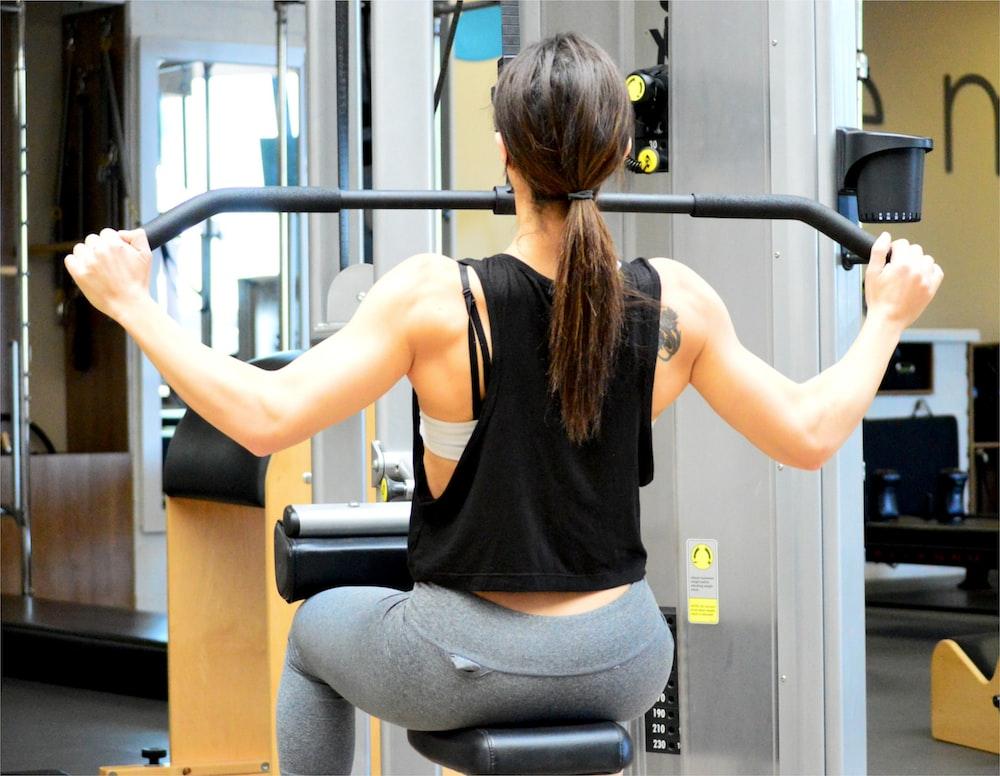 woman wearing black sleeveless top using gym equipment