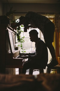 person sitting while playing piano while other man standing on stool while taking picture of person's hand on piano inside room