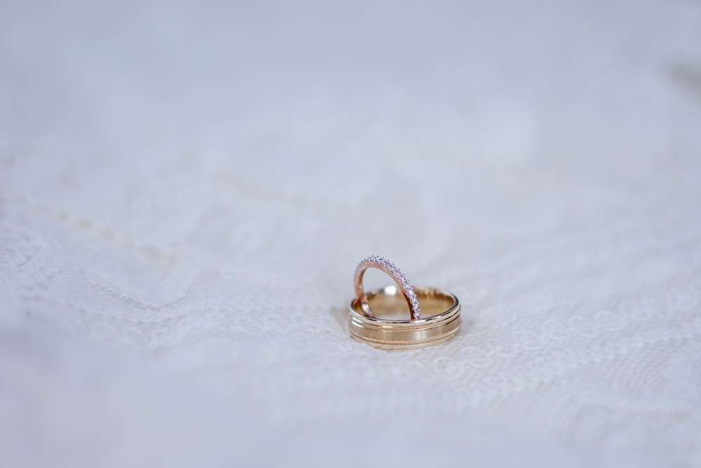 gold-colored ring on white surace