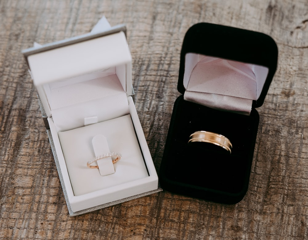 два золотых кольца внутри футляров размещаются на коричневой поверхности