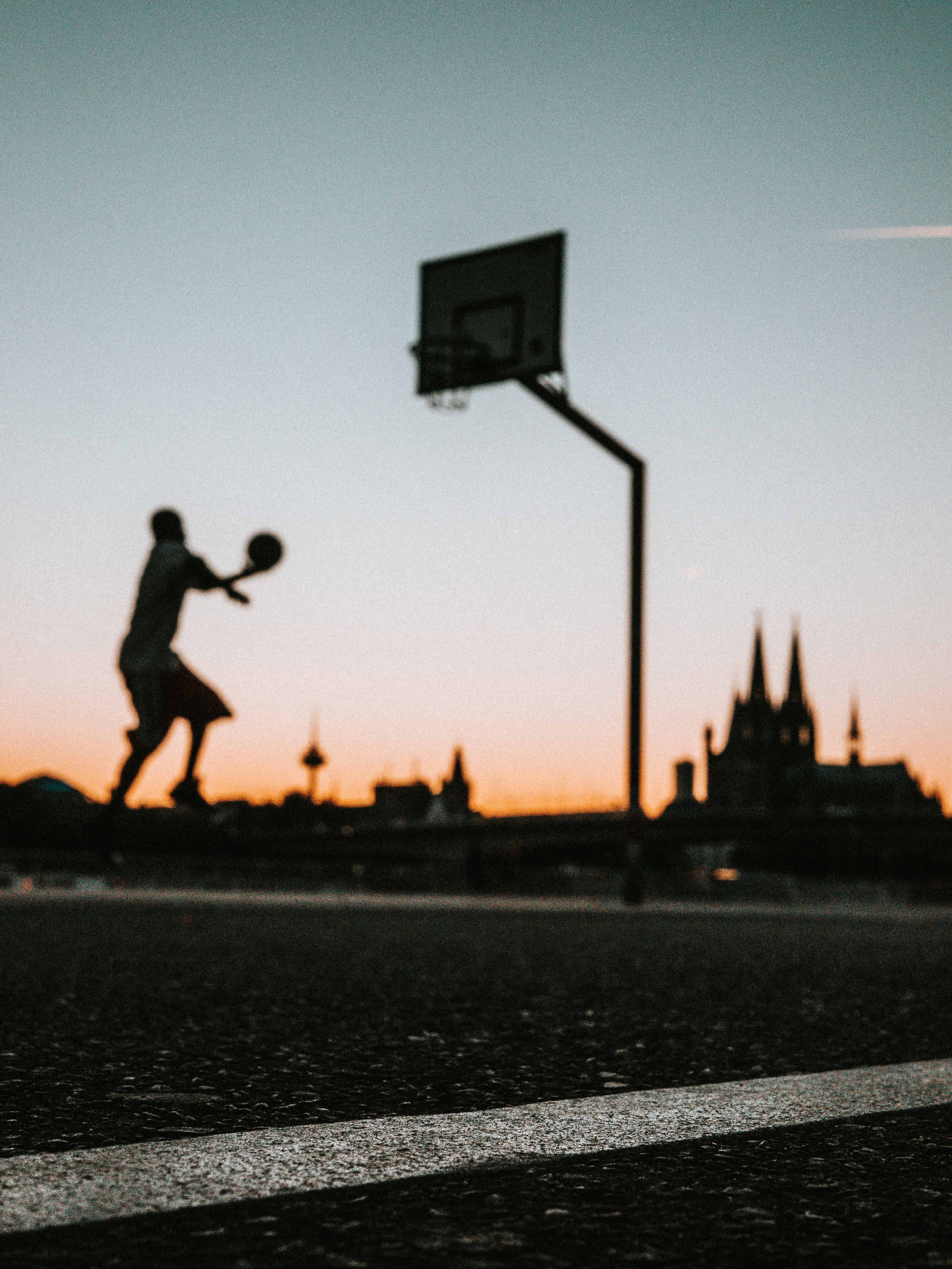 man holding ball jumping near portable basketball hoop
