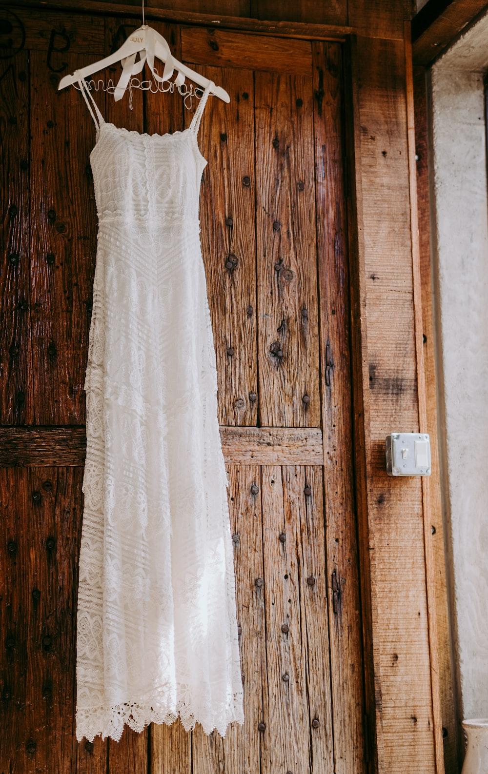 white sleeveless dress near brown wooden door