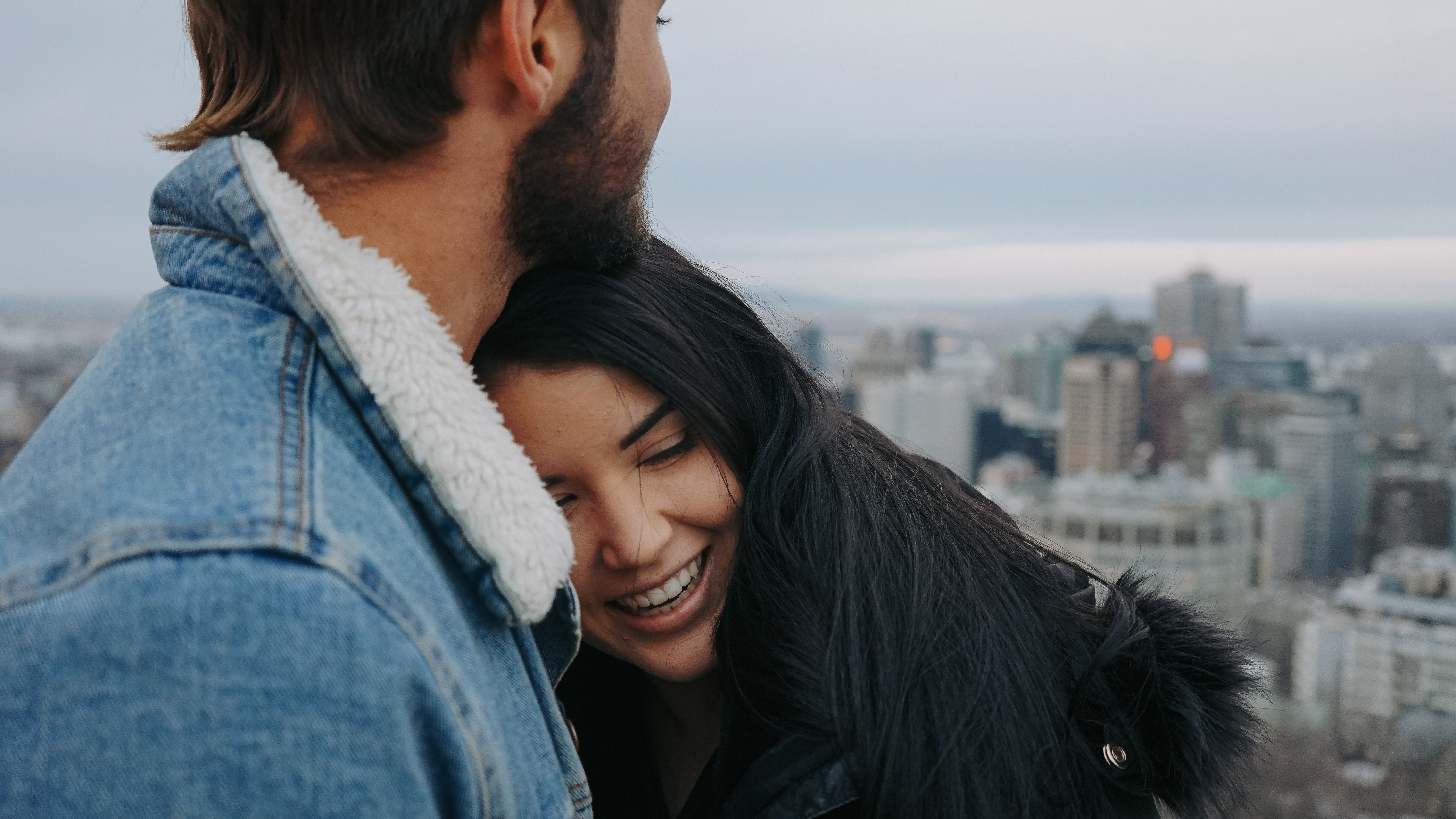 man and woman cuddling on rooftop