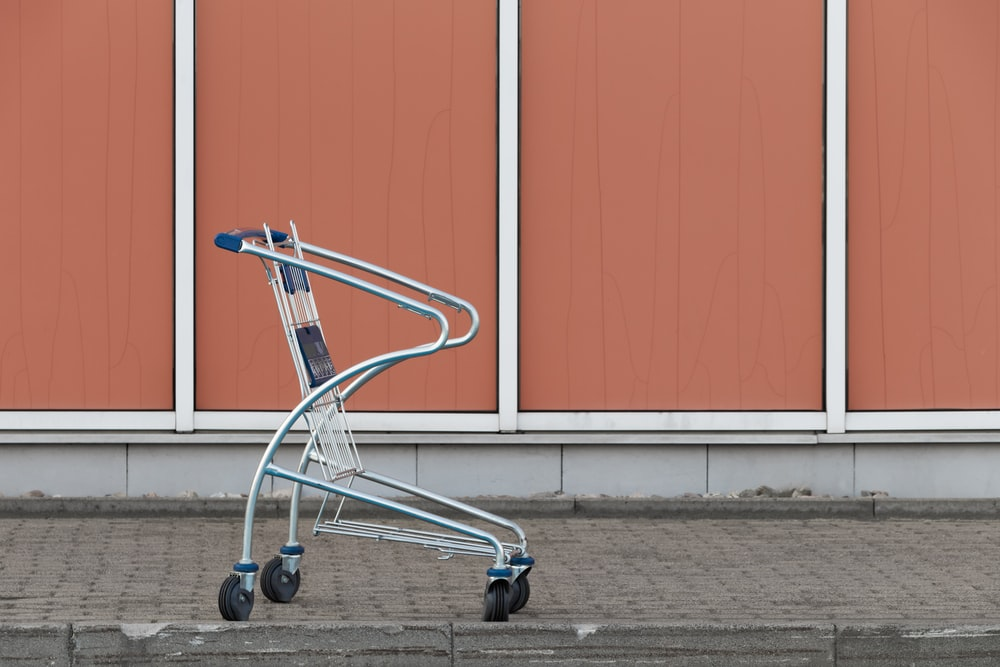 gray shopping cart beside wall