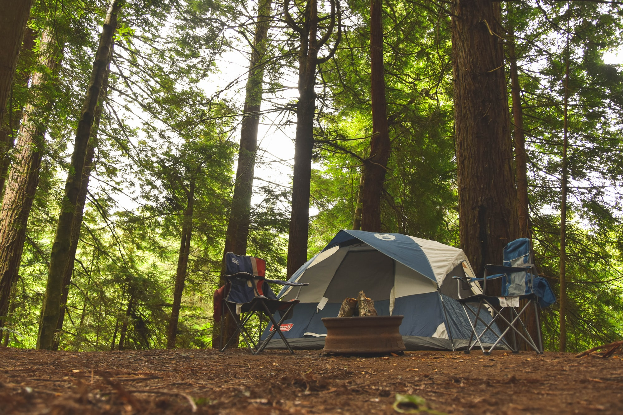 camping in woods with tent and two camp chairs