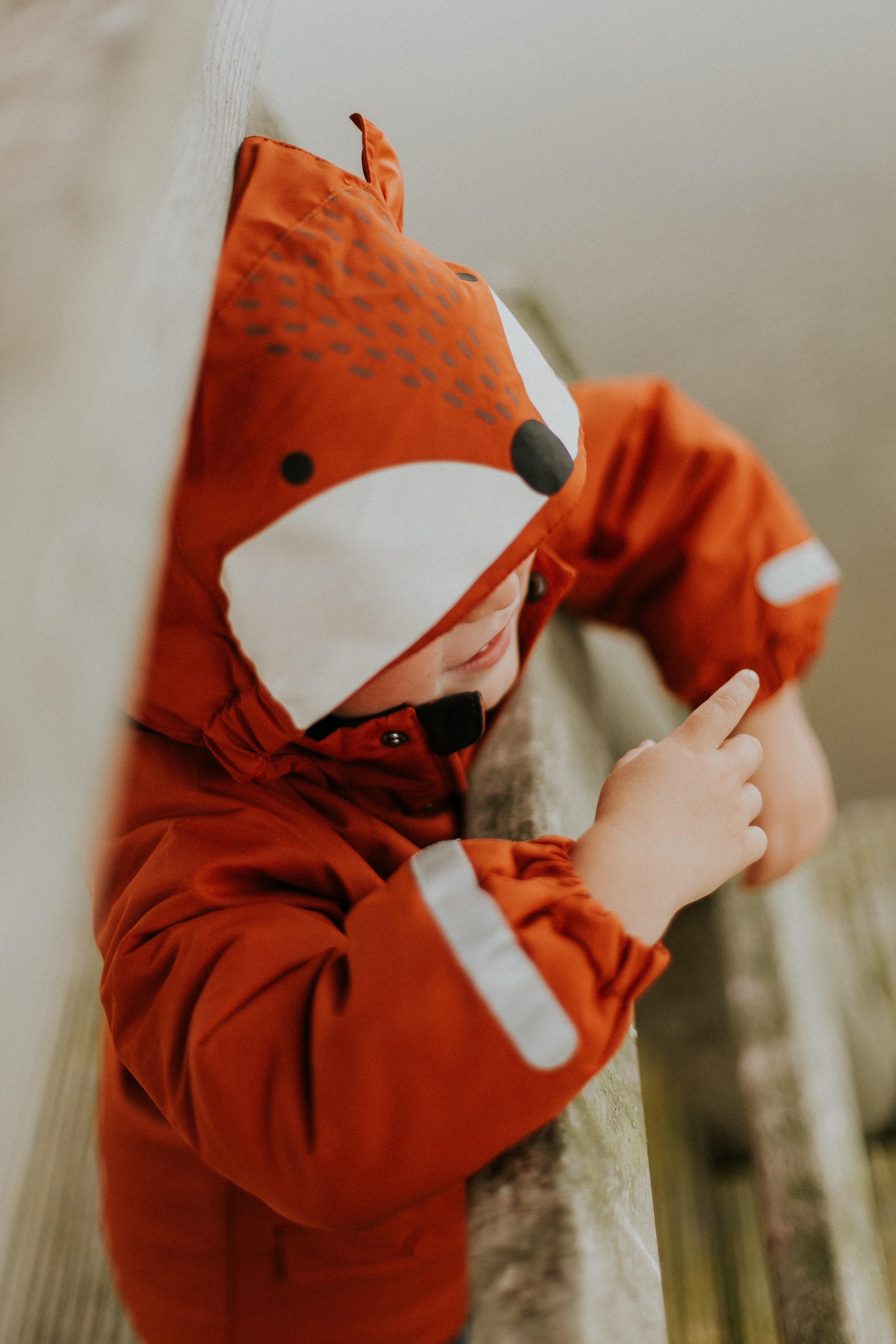 selective-focus photography of toddler wearing orange fox jacket