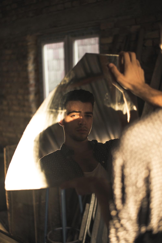 man facing direction of camera from broken mirror