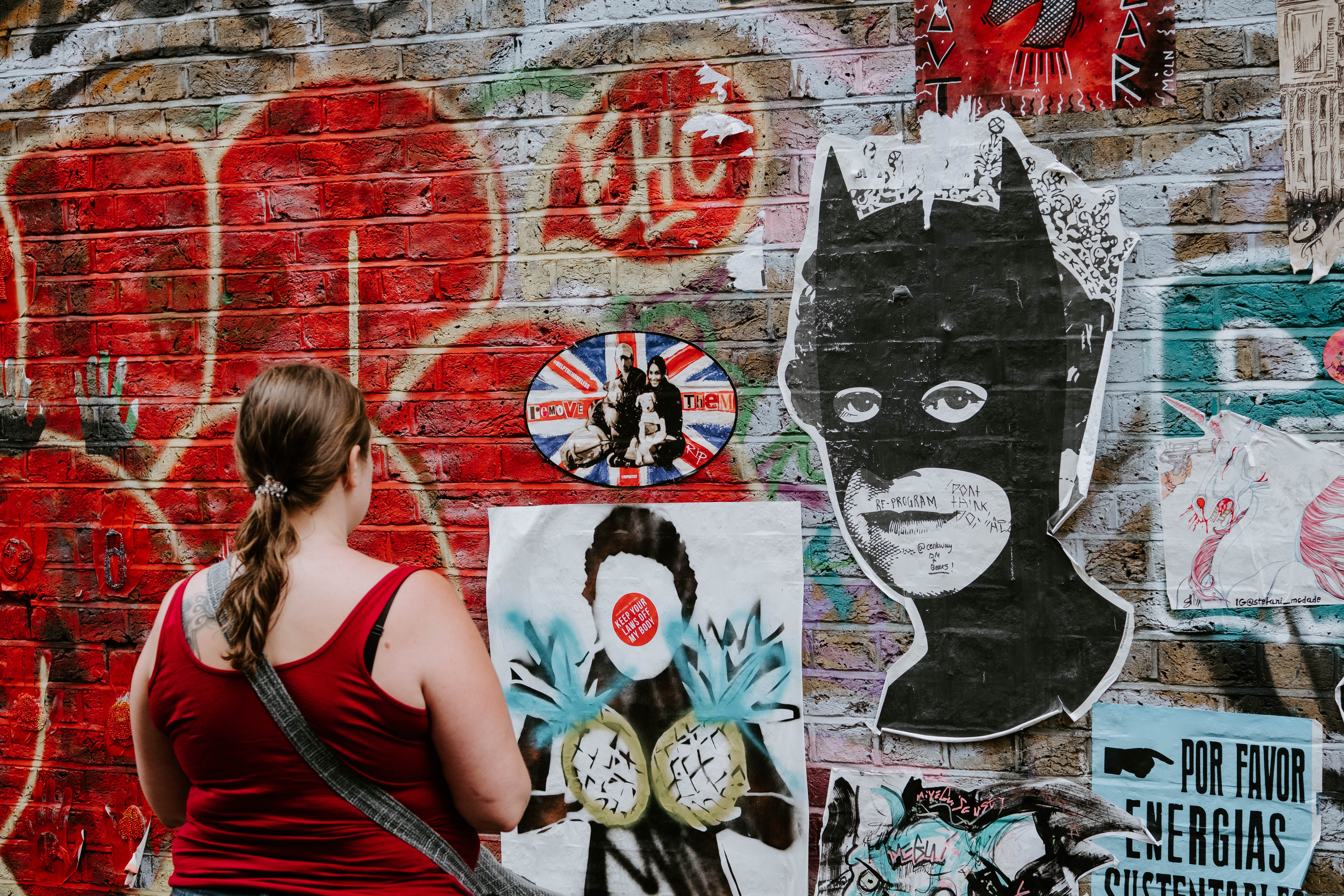 woman looking at batman graffiti wall art