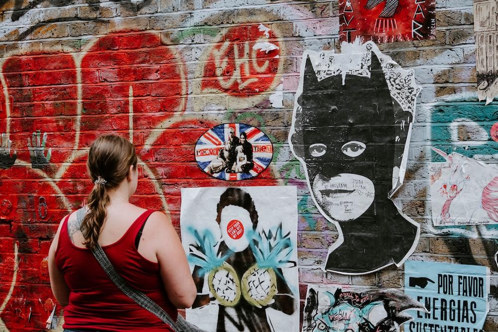 woman looking at batman graffiti wall art