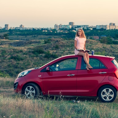 woman sitting on top of a red hatchback car