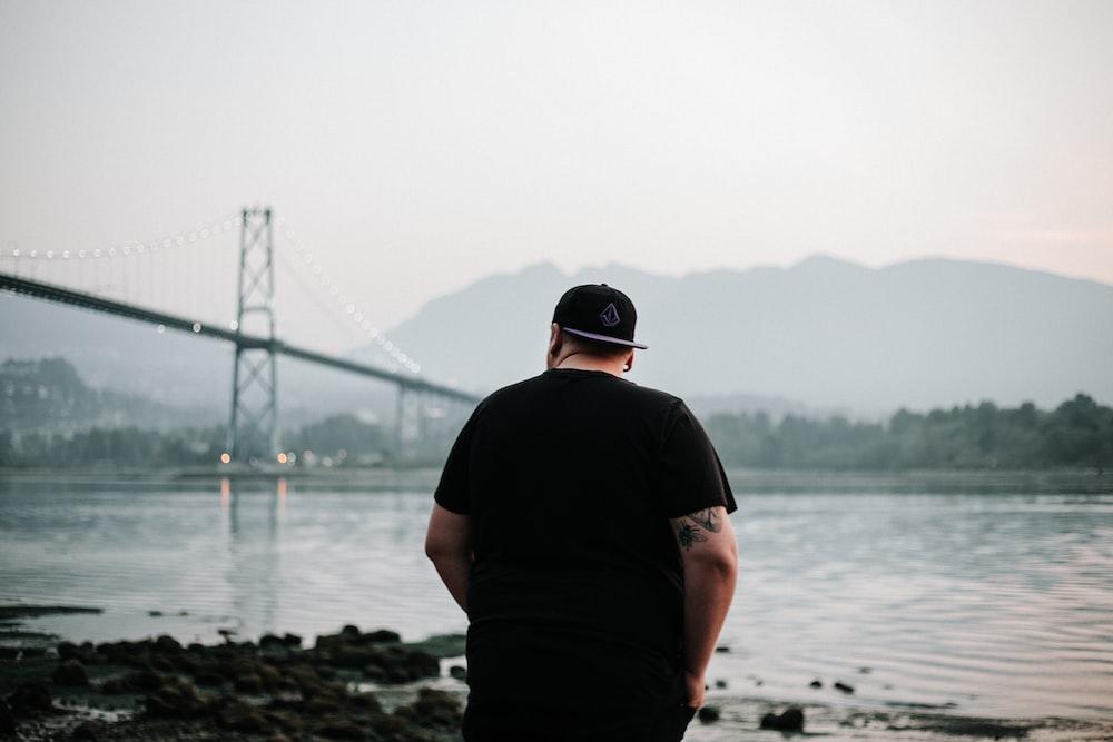 man in black shirt standing near body of water