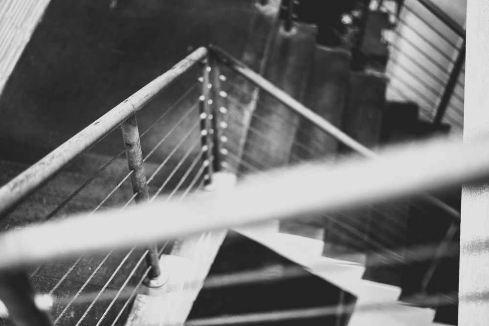 grayscale photo of metal stair railings