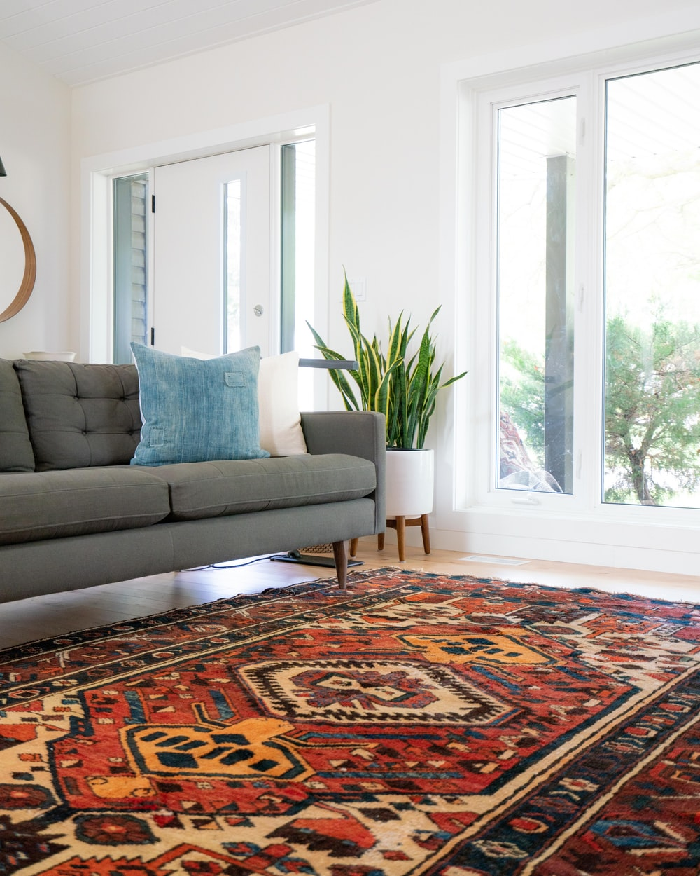 teal 2-seat couch and red area rug