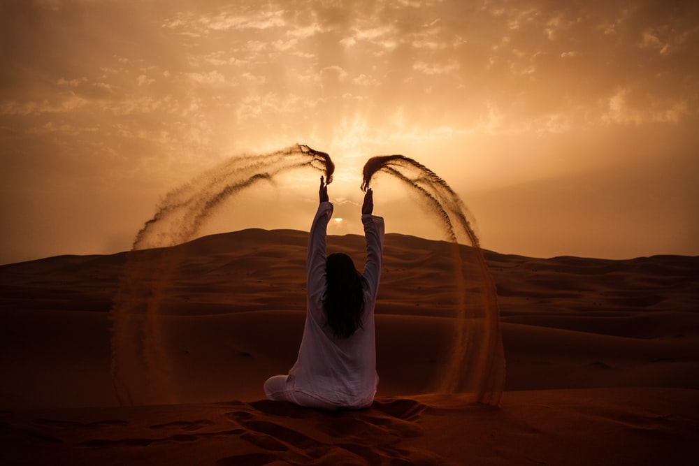 woman sitting on desert while playing sand during golden hour