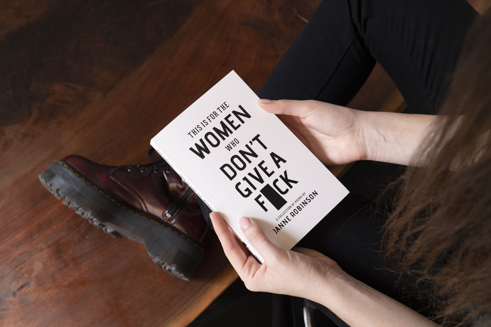 woman holding This is for the women who don't give a fuck book