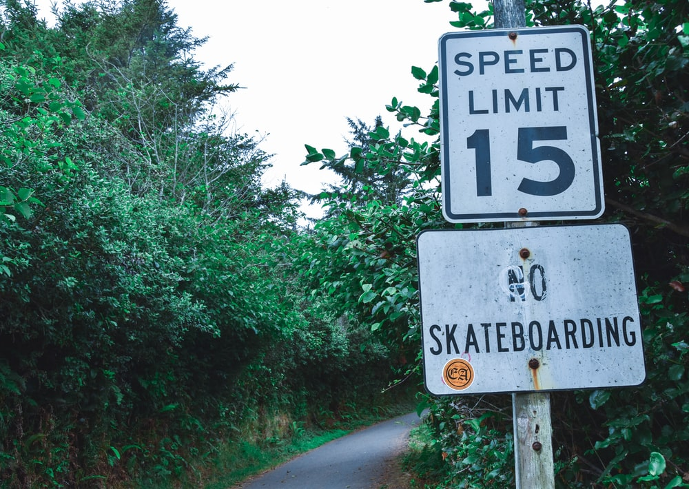 two white speed limit and no skateboarding signages near stree