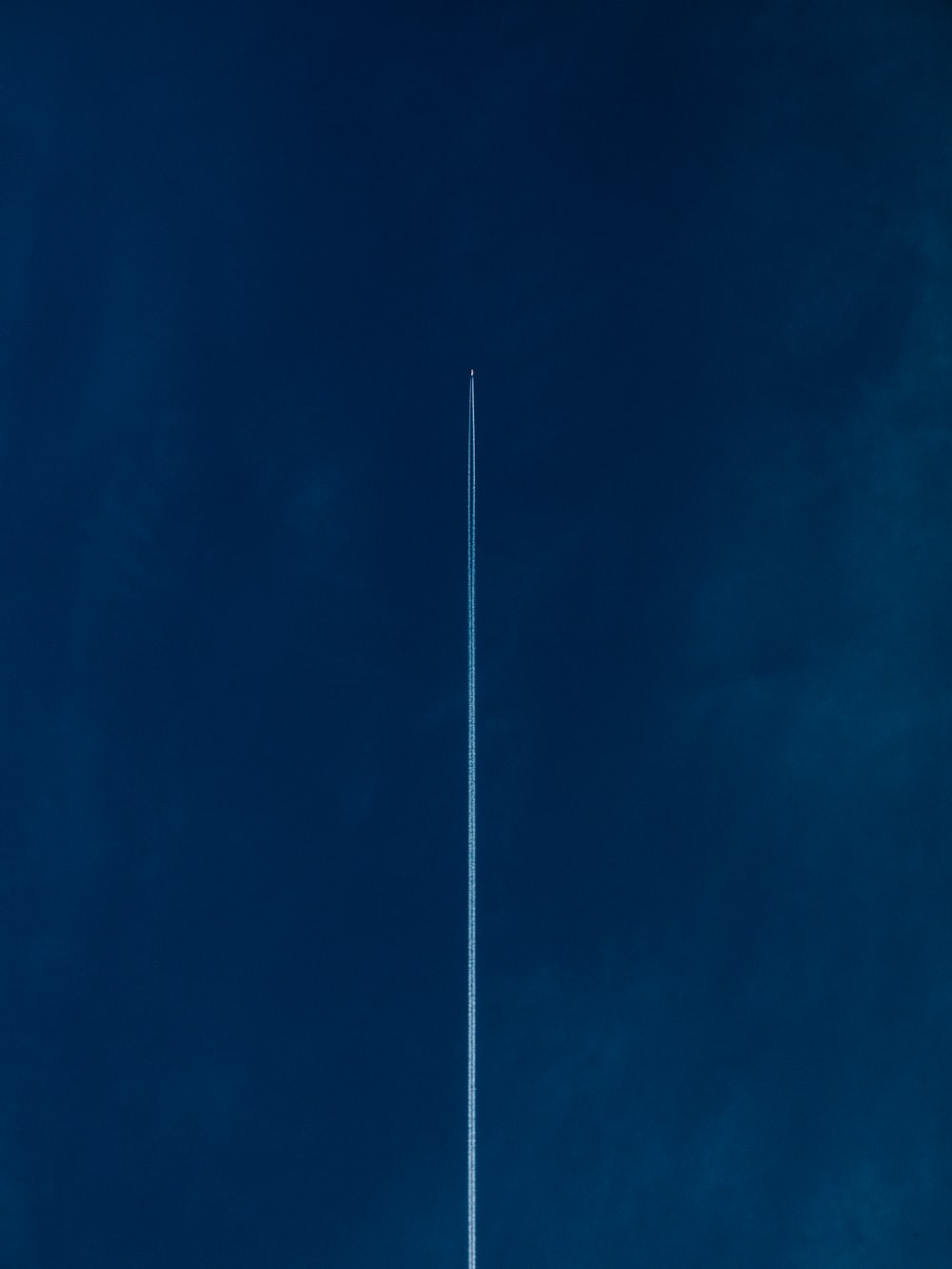 aircraft with line of air on blue sky