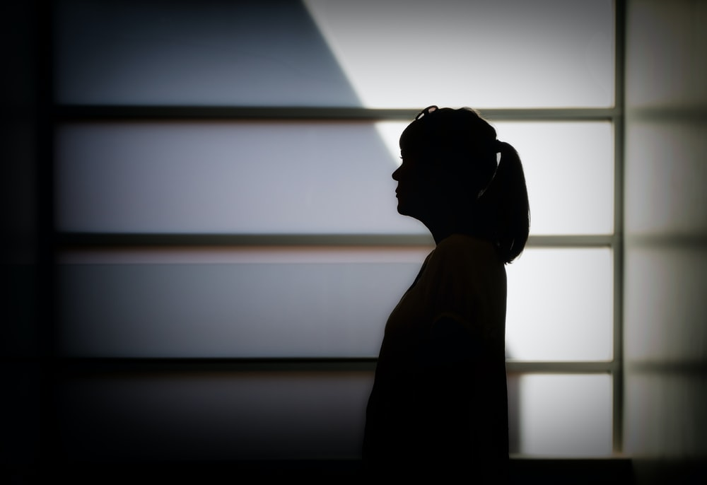 silhouette photo of woman standing near white framed glass window