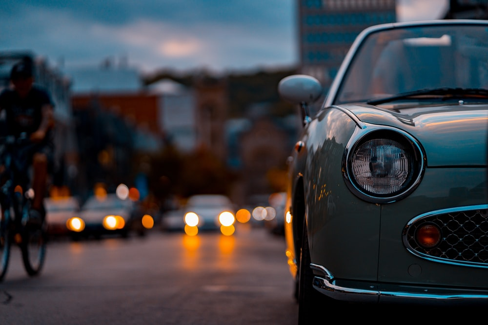 selective focus photography of white car beside road