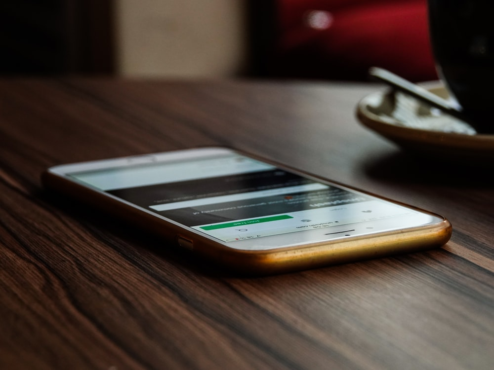 gold iPhone 6 on brown wooden surface