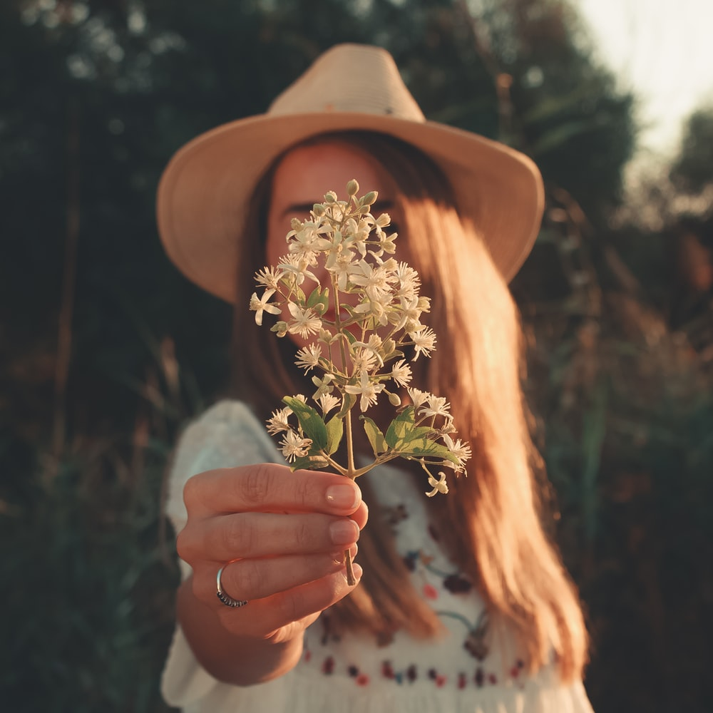 woman handing white flowers to the photographer