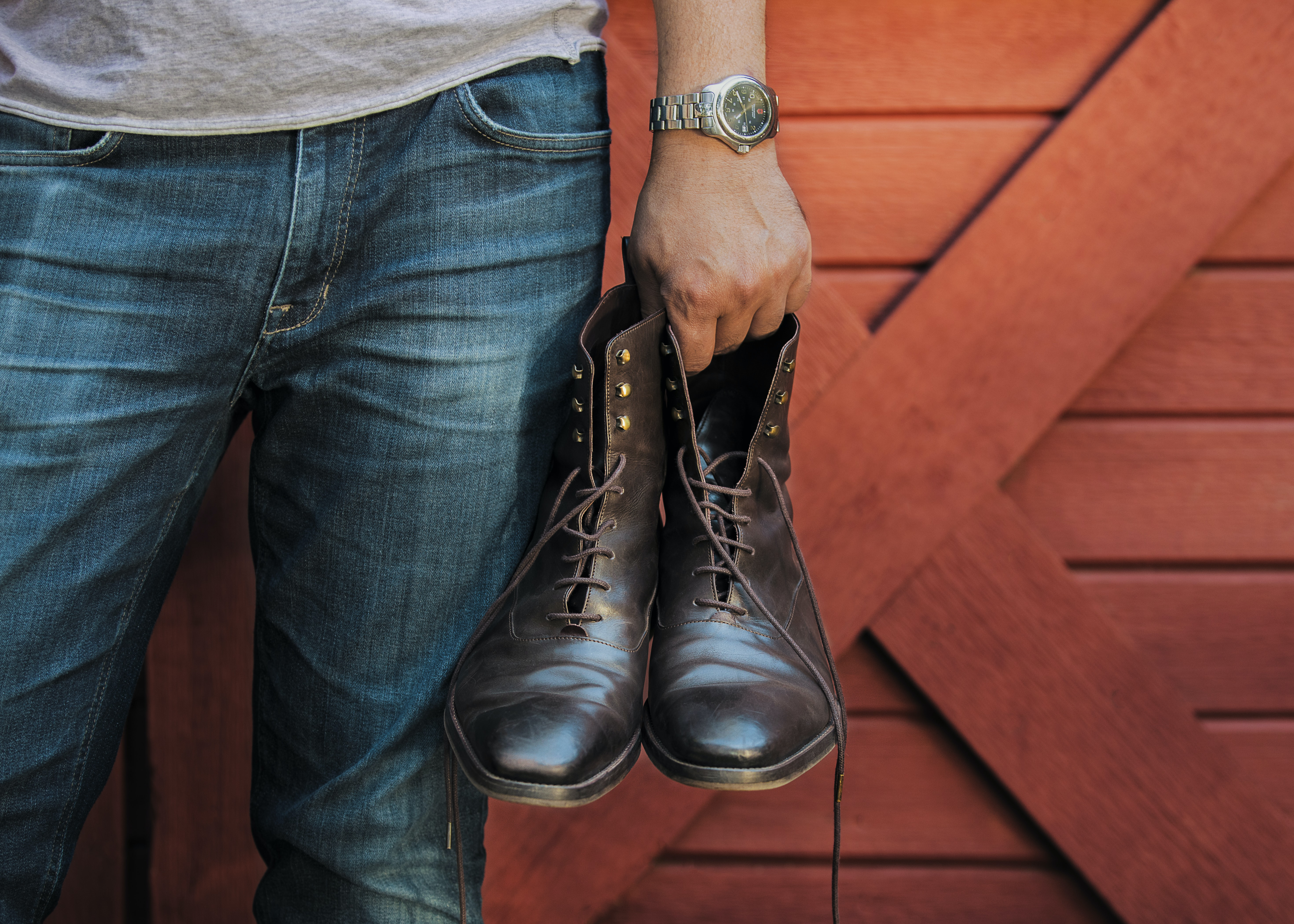 person holding black leather boots beside red barn door panel