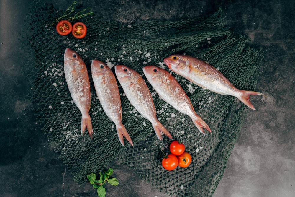 five fish between tomatoes on black net