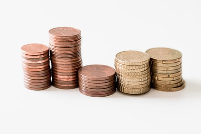 stacked round gold-colored coins on white surface coins zoom background