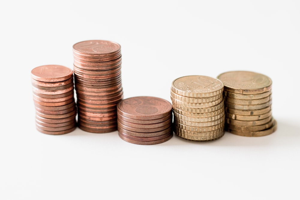 stacked round gold-colored coins on white surface