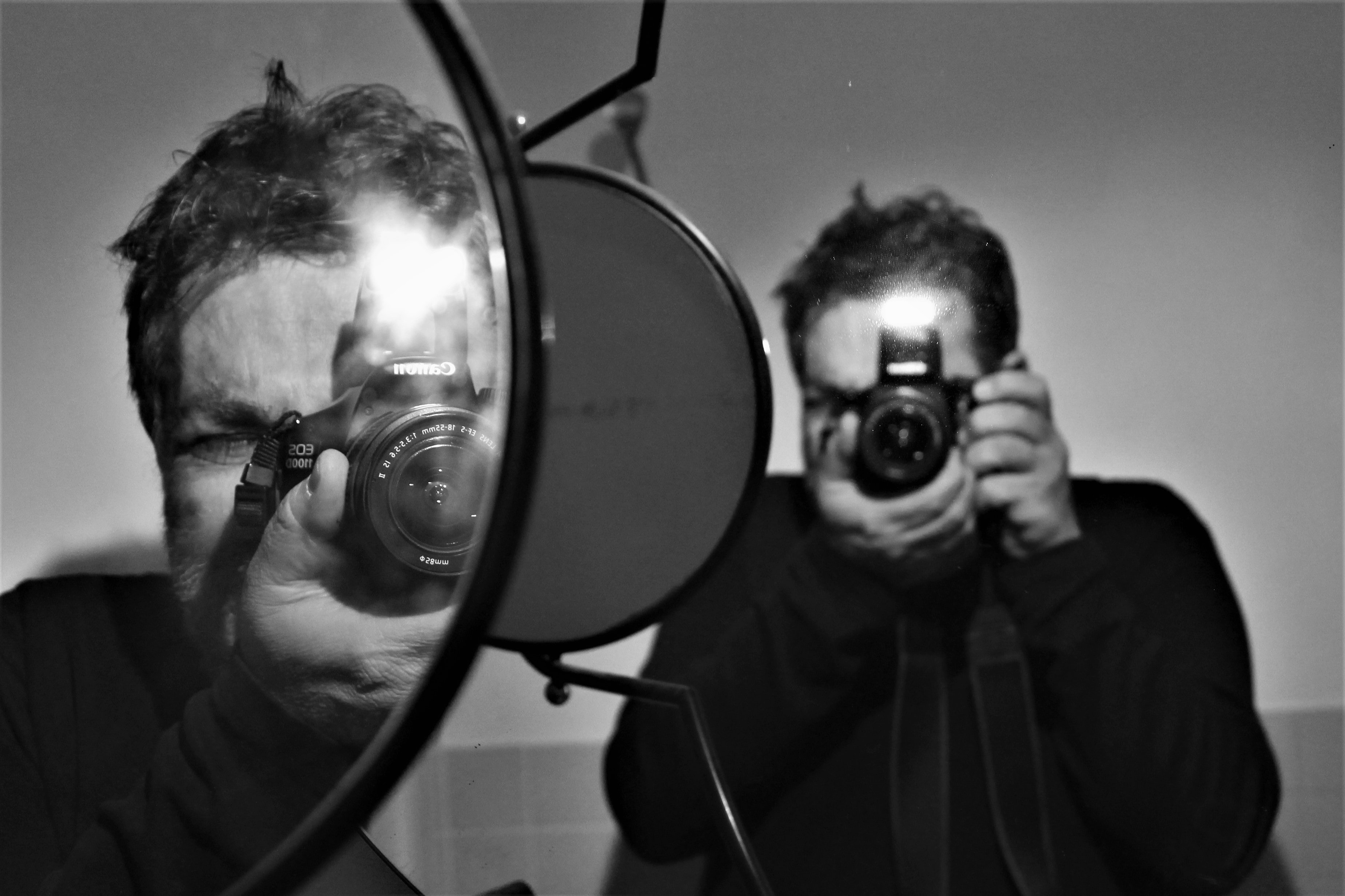 grayscale photography of man holding DSLR camera